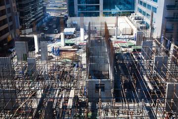 DUBAI, UAE - FEBRUARY, 2018: laborers working on modern construction site works in Dubai. Fast urban development concept.