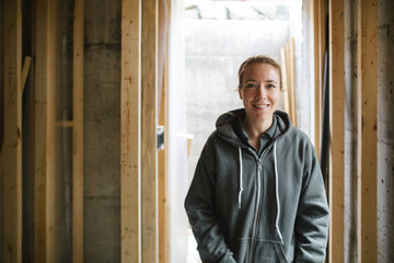 Portrait of young electrician woman smiling at camera on jobsite