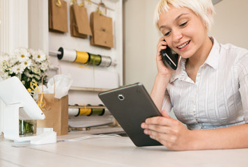 Shop: Woman On Cell Phone While Using Digital Tablet