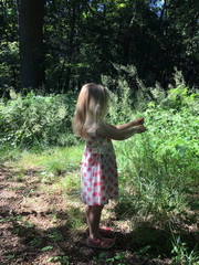 Young girl with blond hair wearing a polka dot pink dress, looking at grasses in woodland.