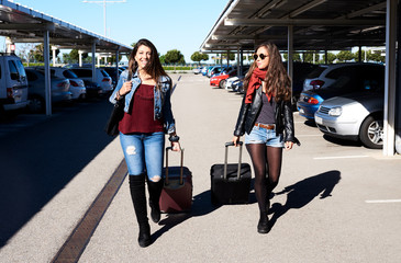 Happy girlfriends walking with their luggage from car parking.
