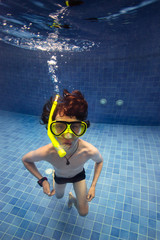 Boy with a snorkel and mask blowing bubbles under water
