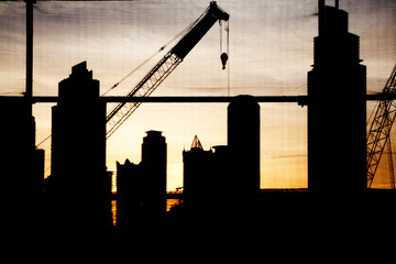 abstract photo of construction site with crane and skyscrapers in Dubai downtown at sunset - fast growing city concept