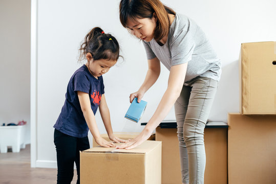 Adorable girl and her mother packing cardboard boxes at new home