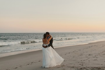 Bride and Groom Kissing on a Beach at Sunset