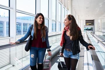 Happy girls on speedwalk in airport.