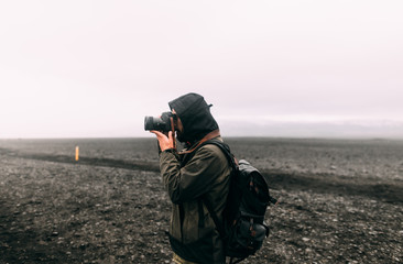 man taking a photo tho the black beach landscape of vik, iceland