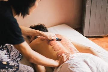Local Thai therapist giving massage to a young tourist