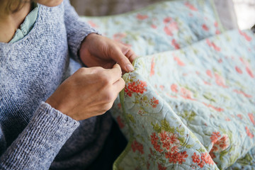 Woman sewing a quilt by hand