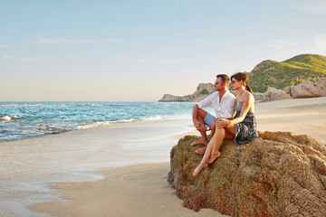 Couple sitting on rock at beach at sunset on vacation in Mexico
