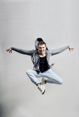 Dancer jumping against a gray background in the studio