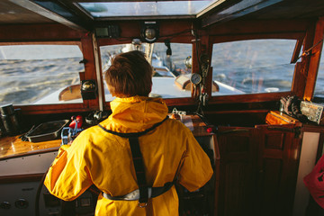 Captain behind steering wheel of a boat in rough weather wearing a yellow raincoat