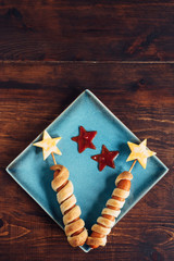 Two firework-themed hotdogs on a plate