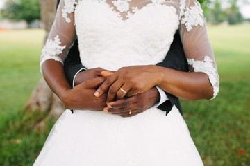 Just married! Clasped hands with wedding rings.