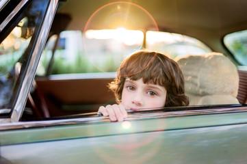Boy sitting in a car with window open