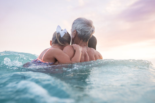 Two Children Hold On To Their Grandparent In The Ocean