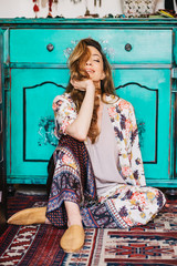 Beautiful female model in bohemian pajama enjoy her time on the floor at home