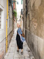 Young female walking down narrow street