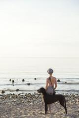 Woman walking dog at sea