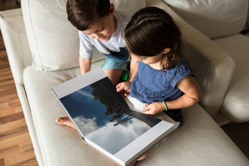 Brother and Sister Admiring A Family Photo Album
