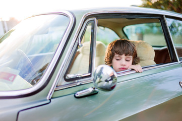 Boy looking at himself in side mirror of car