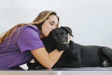 Happy nurse kissing a dog in the vet clinic