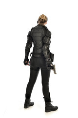 full length portrait of female  soldier wearing black  tactical armour, holding a gun, isolated on white studio background.