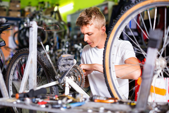 Man repairing bicycles with instruments indoors