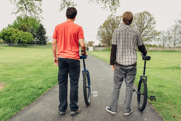 Rear view of two unicycle riders standing with unicycles on road