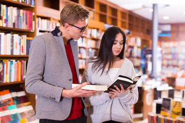 Handsome student choosing book in library