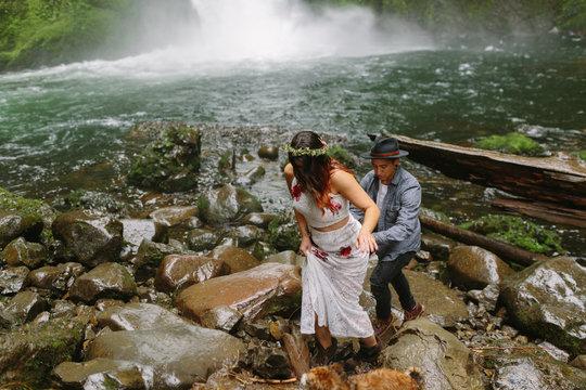 Adventurous Couple Hiking on Rocks by Waterfall