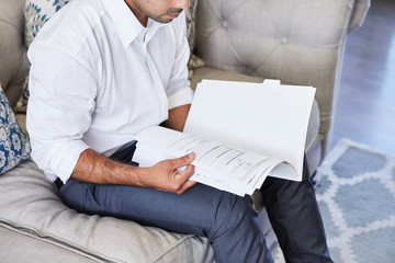 Hispanic businessman reading a contract in a folder at home on the sofa in living room