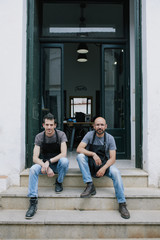 Portrait of two  artisans and owners at the front door of their atelier
