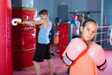 Girl in gloves posing during boxing training at gym