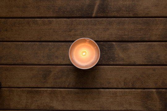 Burning candle on the background of wooden table . The view from the top