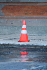 road traffic cones with orange and white stripes standing by the side of the road