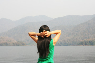 Asian woman  relaxing at the lake with mountain view in holiday tri