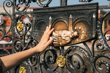Woman tourist touches a bronze statue of John of Nepomuk on the Charles bridge in Prague, Czech Republic for good luck. Legends.