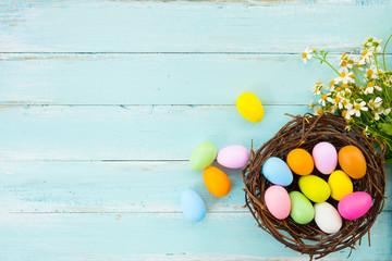 Wall Mural - Colorful Easter eggs in nest with flower on rustic wooden planks background in blue paint. Holiday in spring season. vintage color tone style. top view composition.
