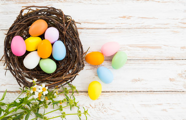 Wall Mural - Colorful Easter eggs in nest with flower on rustic wooden planks background in white paint . Holiday in spring season. vintage color tone style. top view composition.
