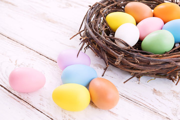 Wall Mural - Colorful Easter eggs in nest on rustic wooden planks background. Holiday in spring season. vintage pastel color tone. Close up composition.