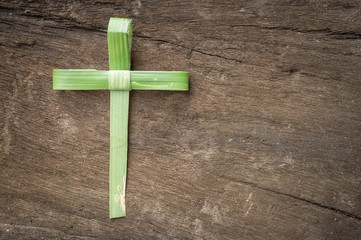 Palm sunday concept: Cross shape of palm branch on an antique wood