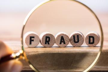 Person Examining Fraud Blocks Through Magnifying Glass