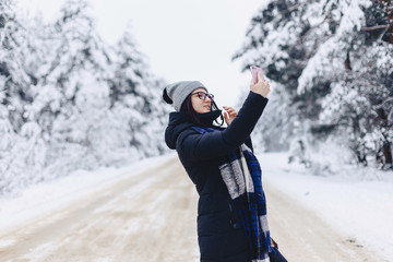 A pretty girl makes a selfie in the middle of a snowy forest road