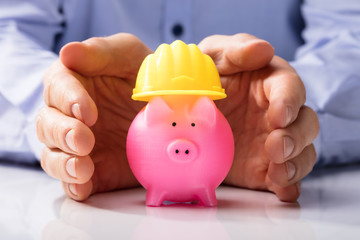 Person Protecting Hard Hat And Piggy Bank