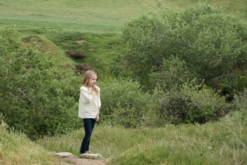 Young girl standing on hillside smelling flower