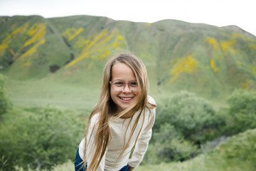 Young, Happy Pretty, Smiling Girl wearing Glasses with Hair Blowing in the Wind and rolling. green hills in the background