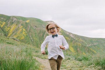 Cute, stylish boy in glasses and bow tie running in a field with rolling green hills behind him
