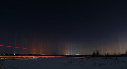 Multicolored radiance in the atmosphere. Natural phenomenon in the night sky over the highway.