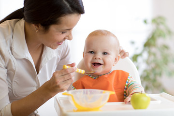 Mom giving homogenized food to her baby son on high chair.